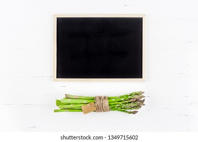 Creative flat lay top view mockup of fresh green asparagus with chalkboard frame on white wooden table background copy space Minimal concept mock up for restaurant promo or shopping sale advertisement