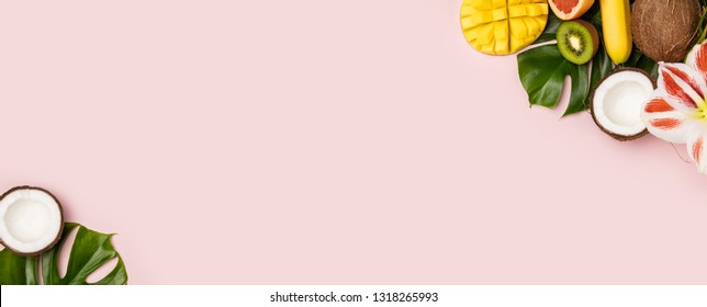 Creative flat lay with tropical fruits and plants on pink background