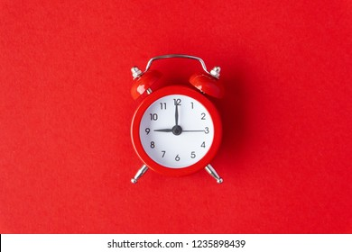 Creative flat lay vintage clock on red color  office table top view background concept retro clock on paper copy space in minimal style, empty template for text, break workplace at noon for lunch.