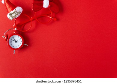 Creative flat lay vintage clock on red office table top view background concept clock on Christmas paper color copy space in minimal style, empty for xmas text, break holiday at noon for lunch.