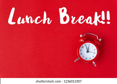 Creative flat lay vintage clock on red office table top view background concept alarm clock on red paper color copy space in minimal style, empty template for text, break workplace at noon for lunch.