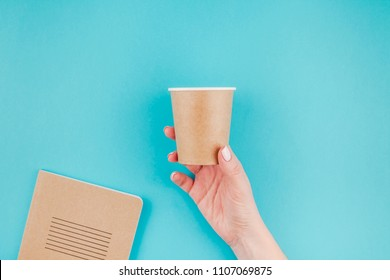 Creative flat lay of woman hand holding craft paper coffee cup and notebook diary with copy space on turquoise background in minimalism style. Template for feminine blog, social media
