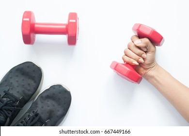 Creative flat lay of woman hand holding red dumbbell with sport items on white background