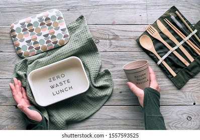 Creative flat lay, zero waste packed lunch concept, reusable wooden cutlery, lunch box in cotton cloth and reusable coffee cup. Sustainable lifestyle top view, flat layout on aged wooden table.