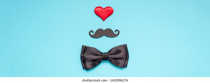 Creative flatlay overhead top view retro stylish black paper moustaches bow tie red heart turquoise background copy space. Men health awareness month fathers day masculinity concept long wide banner