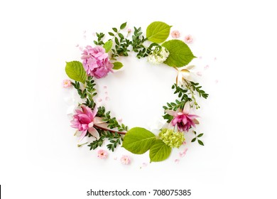 creative floral arrangement. round frame with blooming flowers, leaves and petals on white background. flat lay, top view.