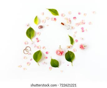 creative floral arrangement. round frame with blooming flowers, leaves and petals on white background. flat lay, top view