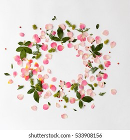 Creative floral round frame with rose petals and green leaves arranged on white background. Flat lay, top view