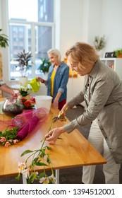 Creative floristry. Nice elderly woman cutting a flower branch while enjoying floristry