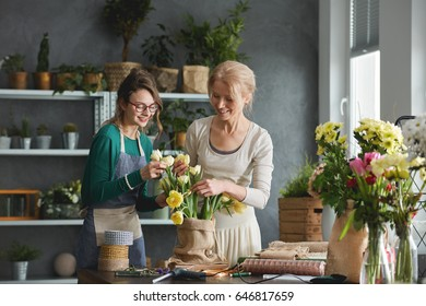 Creative florists preparing tulip bouquet in sack