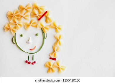 creative food concept, cute girls's face made of ripe vegetables and Italian farfalle pasta