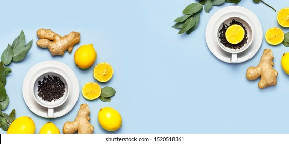 Creative food concept. Fresh ginger root, cup tea with brewing inside, lemon, eucalyptus leaves on blue background. Flat lay top view copy space. Minimalistic style seasoning spice ingredient for tea