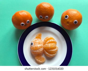 Creative food concept. Googly eyed oranges and a googly eyed goldfish made from orange segments