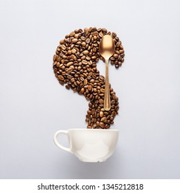 Creative food concept photo of cup of coffee drink beverage beans and golden spoon tableware on grey background.