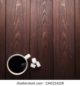 Creative food concept photo of cup of coffee drink beverage and sweet sugar on brown wooden background.
