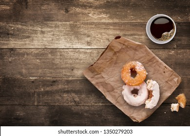 Creative food concept photo of morning lunch break in the office consisted of a cup of black takeaway coffee and tasty donuts on brown wooden background.