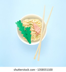 Creative food diet healthy eating concept photo of tasty ramen noodle pasta with shrimps prawns greens chopsticks and bowl on blue background.