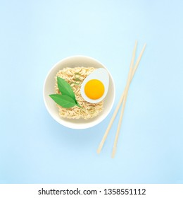 Creative food diet healthy eating concept photo of tasty ramen noodle pasta with egg greens chopsticks and bowl on blue background.