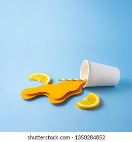 Creative food health diet concept photo of take away cup with splashing orange juice drink beverage made of paper with straw and orange slices on blue background.