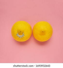 Creative food health fashion concept photo of lemons in shape of woman breast with nipple piercing on pink background.