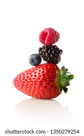 Creative food healthy eating diet concept photo of colourfull pyramid made of fresh summer berries full of vitamins strawberry raspberry blueberry blackberry on white background.