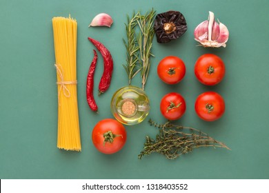 Creative food poster with flat lay knolling of Italian arrabiata pasta ingredients. Spaghetti tomatoes hot chili peppers culinary herbs olive oil on green background. Mediterranean diet healthy eating