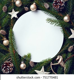 Creative frame of Christmas tree branches and decorations with round blank card. Top view. Xmas and New year concept
