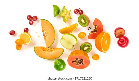 Creative fresh fruits layout. Papaya, apple, orange, kiwi, melon isolated on white background. Fruity diet summer concept. Tropical mix background. Colorful summertime fruit flat lay.