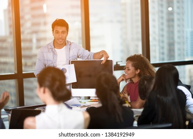 Creative friendly smiling businessmen having conversation sitting together at meeting, cheerful caucasian male executive discuss work in office with multi-ethnic subordinates