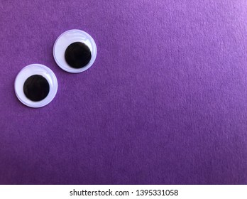Creative fun background, googly eyes isolated on purple with copy space