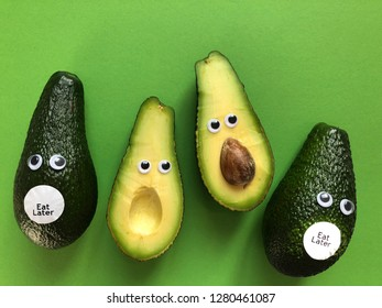 Creative fun healthy food photography. Avocados with googly eyes and Eat Later stickers looking at an avocado cut in half.