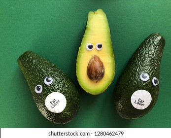 Creative fun healthy food photography. Avocados with googly eyes and Eat Later stickers looking at half an avocado