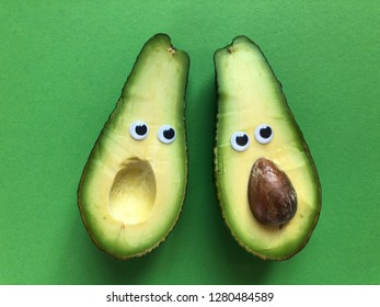 Creative fun healthy food photography. Avocado cut in half with googly eyes, one half with the seed, the other without.