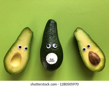 Creative fun healthy food photography. An avocado cut in half with googly eyes, with an avocado with googly eyes and an Eat Later sticker between them.