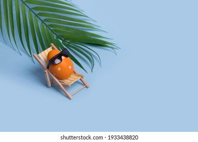 Creative funny composition with Easter egg with sunglasses sitting on deck chair and palm leaf on bright blue background. Trendy minimal spring or summer vacation, holiday and travel concept.