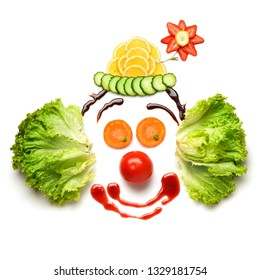 Creative funny diet food healthy eating concept photo of nice funny edible clown face made of fresh fruits and vegetables full of vitamins on white background.
