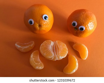 Creative funny fruit concept. Two googly eyed oranges looking at a peeled, segmented orange on an orange background.