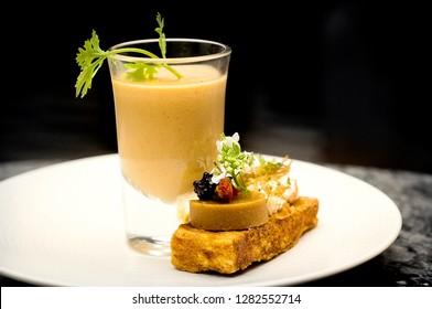 Creative fusion of Thai food. Appetizer Tomyum bisque with mushroom dried tomato kaffir and bread, caviar, foie gras