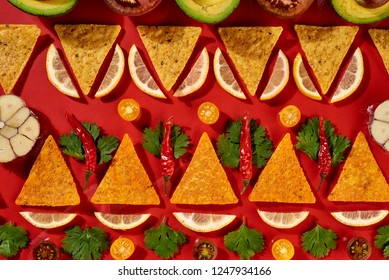 Creative geometric food pattern from mexican nachos corn chips, fresh vegetables, fruits, greens, chili, garlic - ingredients for tomato chili sauce on a red background. Flat lay