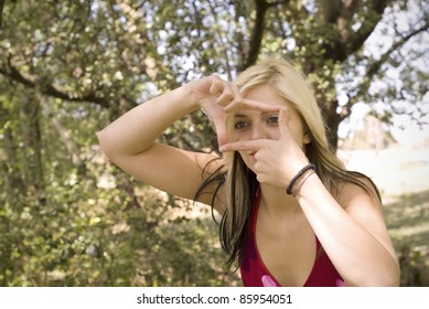 Creative girl or woman photographer framing her photo with finger frame in garden or park