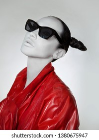 Creative glamor. Young Woman In fashionable red Long lacquer raincoat and sunglasses. Crazy Fashion Make-up, Accessory and Creative Hairstyle. Stylish demon, Total black look. Girl with white face.