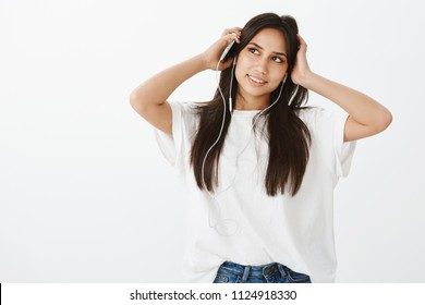 Creative good-looking woman with dark hair in stylish outfit, holding smartphone while hands on head, looking up with dreamy look and listening music in earphones, planning or picturing in mind