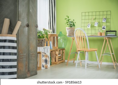 Creative green room with desk, chair, pallets and metal wardrobe