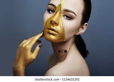 Creative grim makeup face of girl Golden color zipper clothing on skin. Fashion beauty creative cosmetics and skin care halloween. Brunette woman on dark background, beautiful big eyes and smooth skin