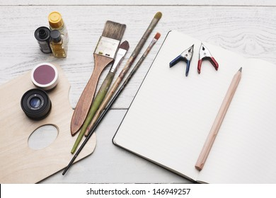 Creative group of object for painting, writing and sketching on a white hardwood table. Studio shot.