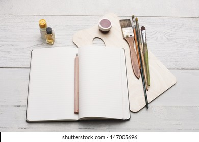 creative group of objects for painting, writing and sketching on a white hardwood table. Studio shot.