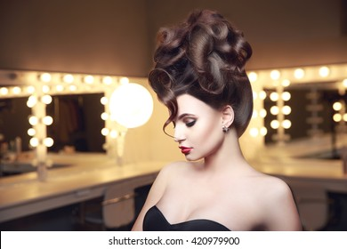 Creative hairstyle of young sexual woman in lingerie. Side view. Makeup room with ligts.