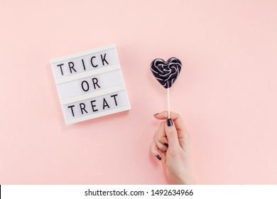 Creative Halloween Day composition flat lay top view holiday celebration sweet black lollipop heart hand lightbox pink paper background copy space Template greeting card design social media