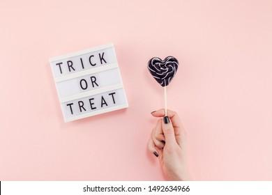 Kreative Halloween-Komposition flach Lay Draufsicht Feiertag süße schwarze Lollipop-Herz Hand Leuchtkasten rosa Papier Hintergrund Kopienraum Vorlage Grußkartendesign soziale Medien
