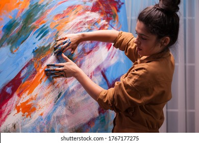 Creative hand painting in art workshop on large canvas. Modern artwork paint on canvas, creative, contemporary and successful fine art artist drawing masterpiece